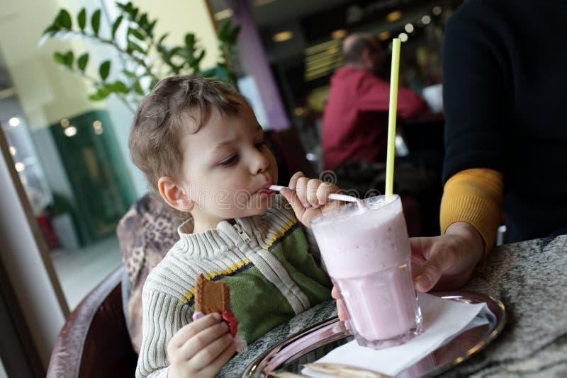 L'enfant boit le smoothie de fraise de lait images libres de droits