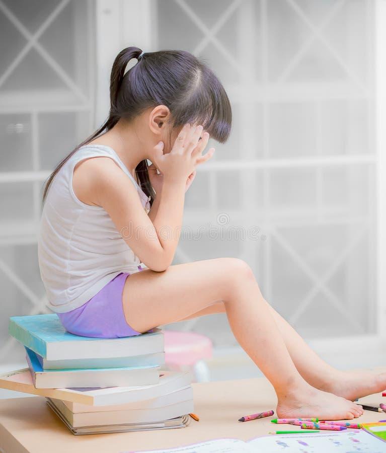 L'enfant bouleversé de problème avec la tête dans des devoirs de mains, d'éducation et de concept d'école est trop pour de petits photo libre de droits