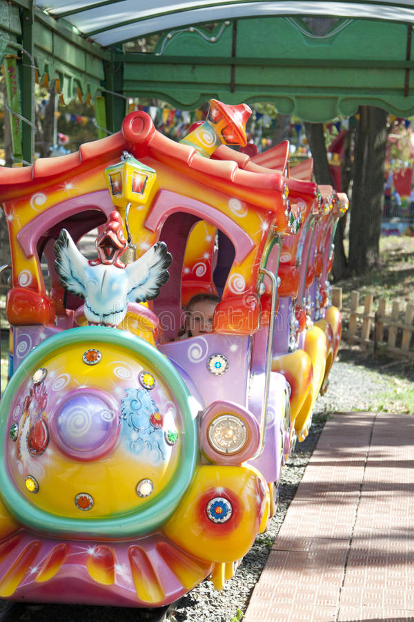 L'enfant conduit dans l'attraction d'été en stationnement. images libres de droits