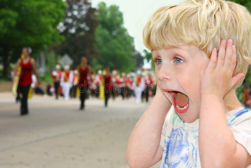 L'enfant couvre des oreilles pendant le défilé bruyant photographie stock libre de droits