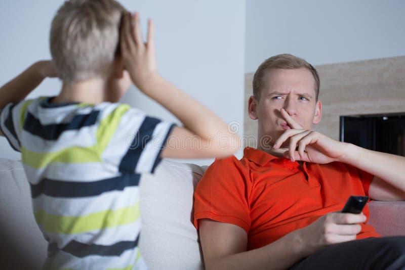 L'enfant dérange son père image stock