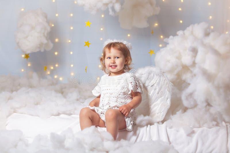 L'enfant d'ange s'assied les regards de nuages image stock