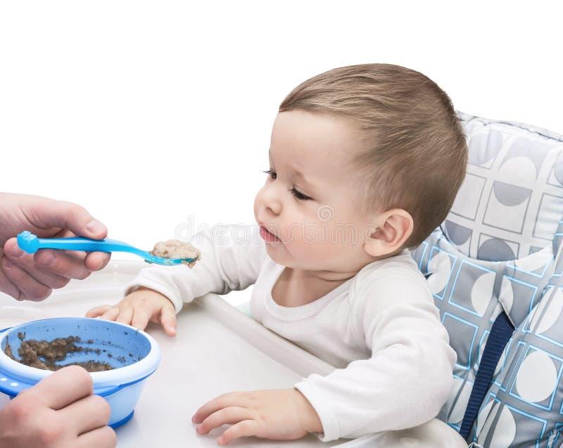 L'enfant d'un an mange du gruau photographie stock
