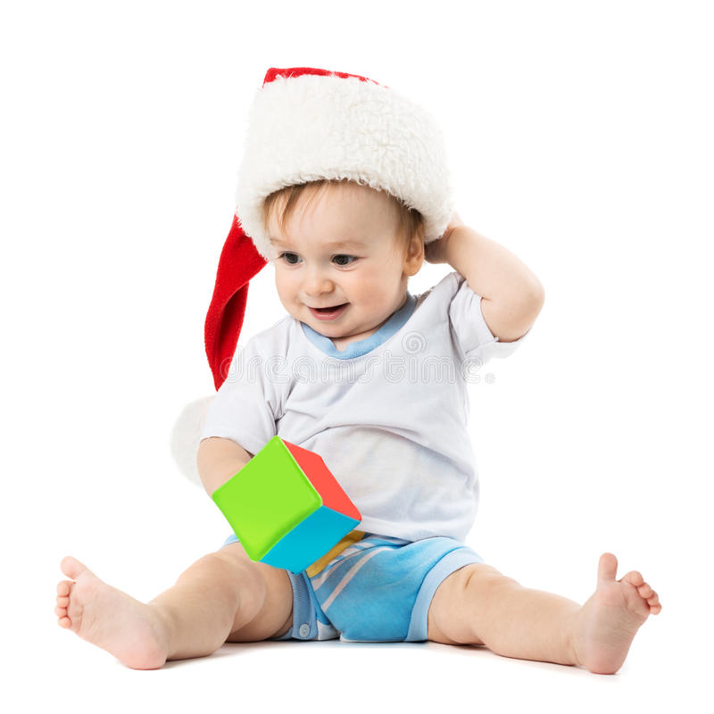 L'enfant dans un chapeau Santa raye sa tête photos stock