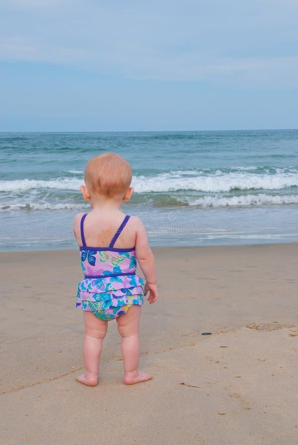 L'enfant de chéri sur la plage regarde fixement l'océan photos libres de droits