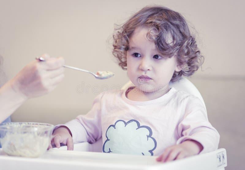 L'enfant de deux ans mange du gruau images stock