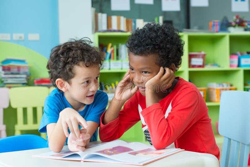 L'enfant de deux garçons s'asseyent sur la table et le livre de conte de lecture dans la bibliothèque préscolaire, concept d'éduc images libres de droits