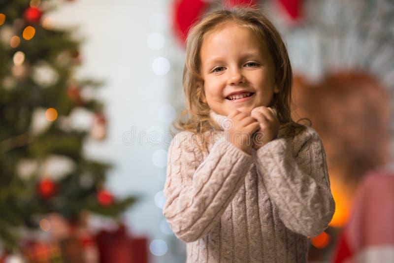 L'enfant de fille à la maison à la cheminée célèbre le Joyeux Noël W images libres de droits