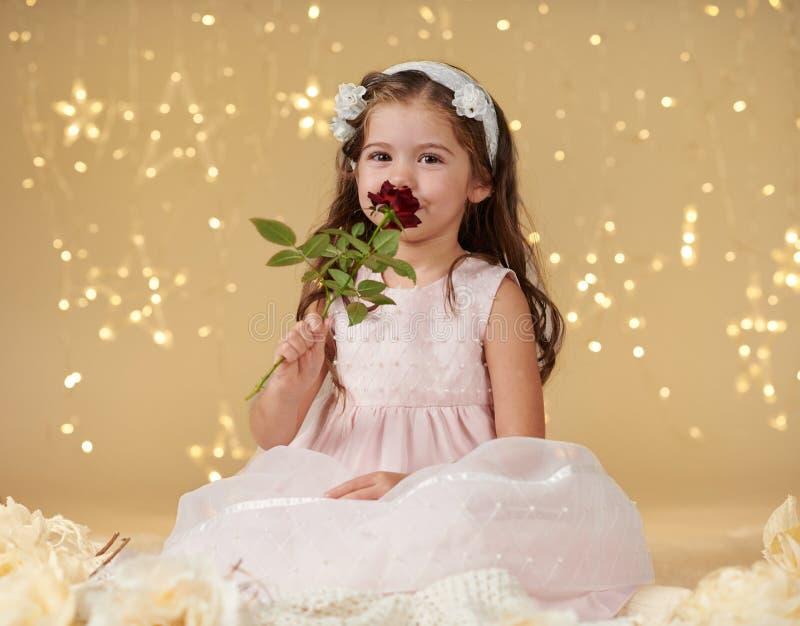 L'enfant de fille avec la fleur rose pose dans des lumières de Noël, fond jaune, robe rose images libres de droits