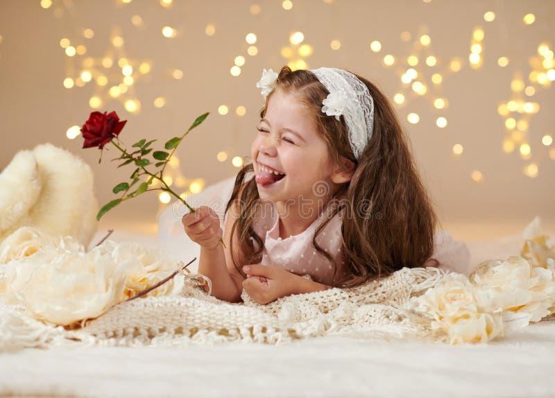 L'enfant de fille avec la fleur rose pose dans des lumières de Noël, fond jaune, robe rose photos stock