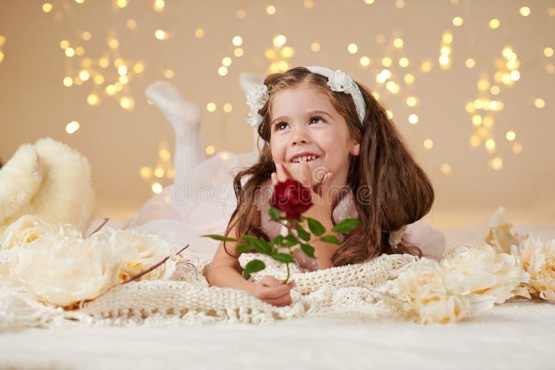 L'enfant de fille avec la fleur rose pose dans des lumières de Noël, fond jaune, robe rose photos libres de droits