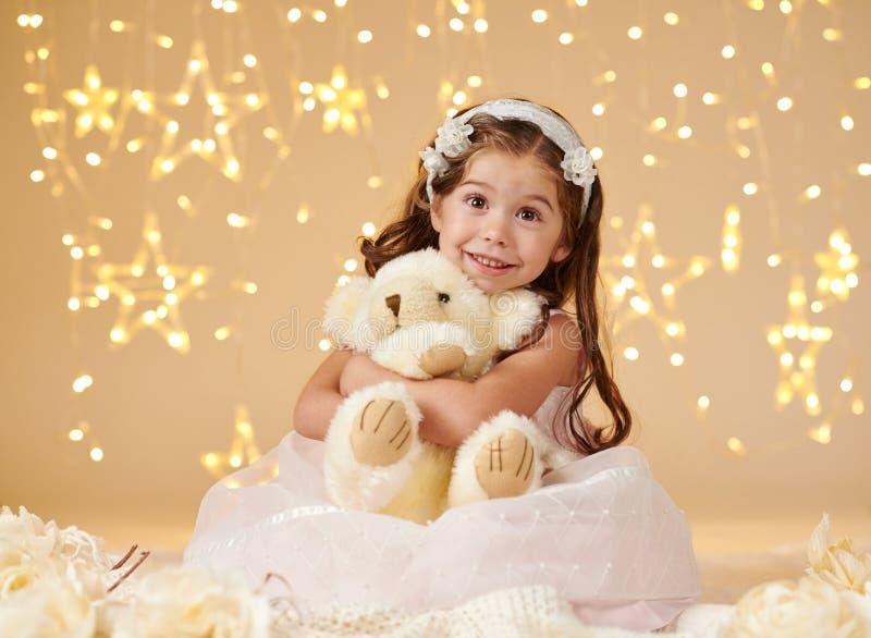 L'enfant de fille avec le jouet d'ours pose dans des lumières de Noël, fond jaune, robe rose photos stock