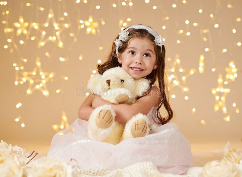 L'enfant de fille avec le jouet d'ours pose dans des lumières de Noël, fond jaune, robe rose photographie stock libre de droits