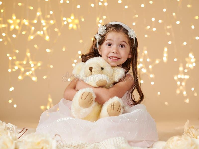 L'enfant de fille avec le jouet d'ours pose dans des lumières de Noël, fond jaune, robe rose images stock
