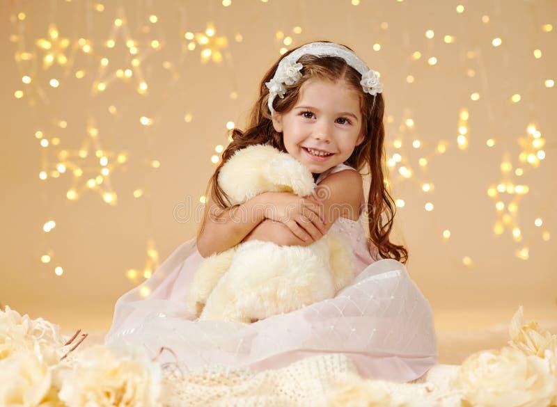 L'enfant de fille avec le jouet d'ours pose dans des lumières de Noël, fond jaune, robe rose photos libres de droits