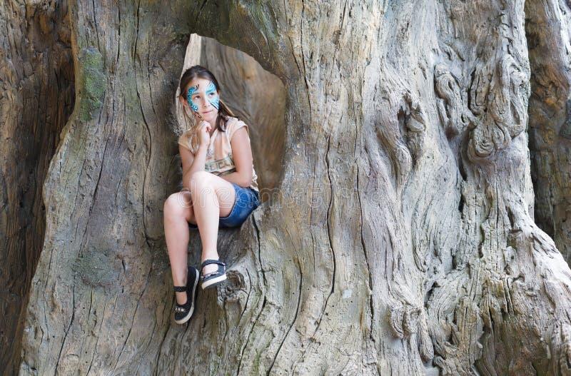 L'enfant de fille dehors s'asseyent dans l'arbre avec la peinture de visage de papillon images stock