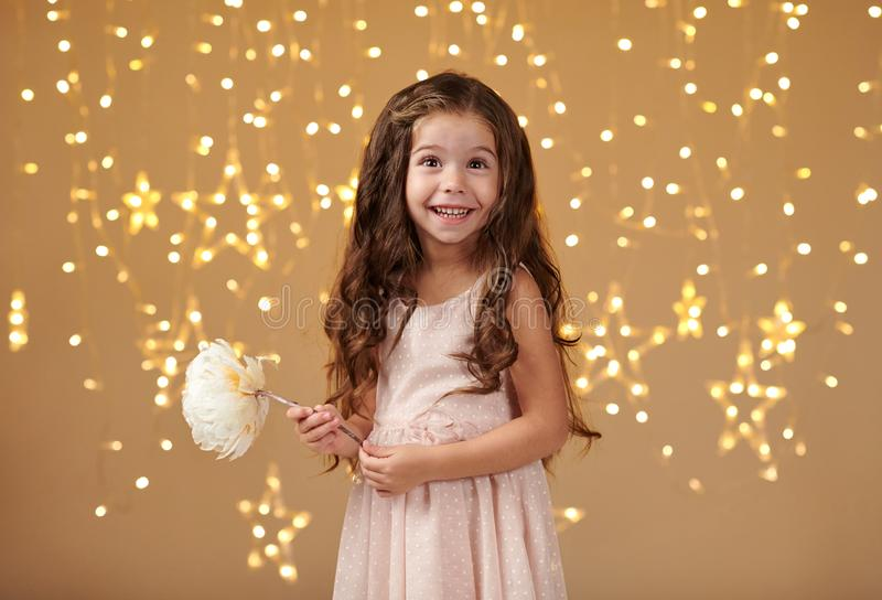 L'enfant de fille est dans des lumières de Noël, fond jaune, robe rose photographie stock libre de droits
