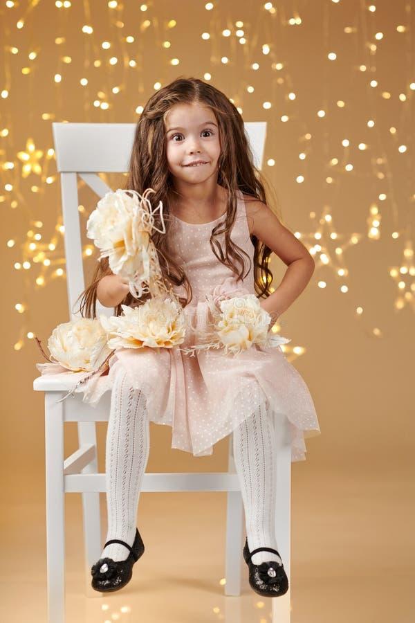 L'enfant de fille est dans des lumières de Noël, fond jaune, robe rose image stock