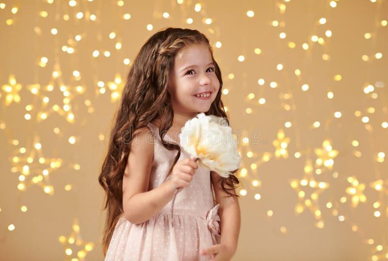L'enfant de fille est dans des lumières de Noël, fond jaune, robe rose photographie stock