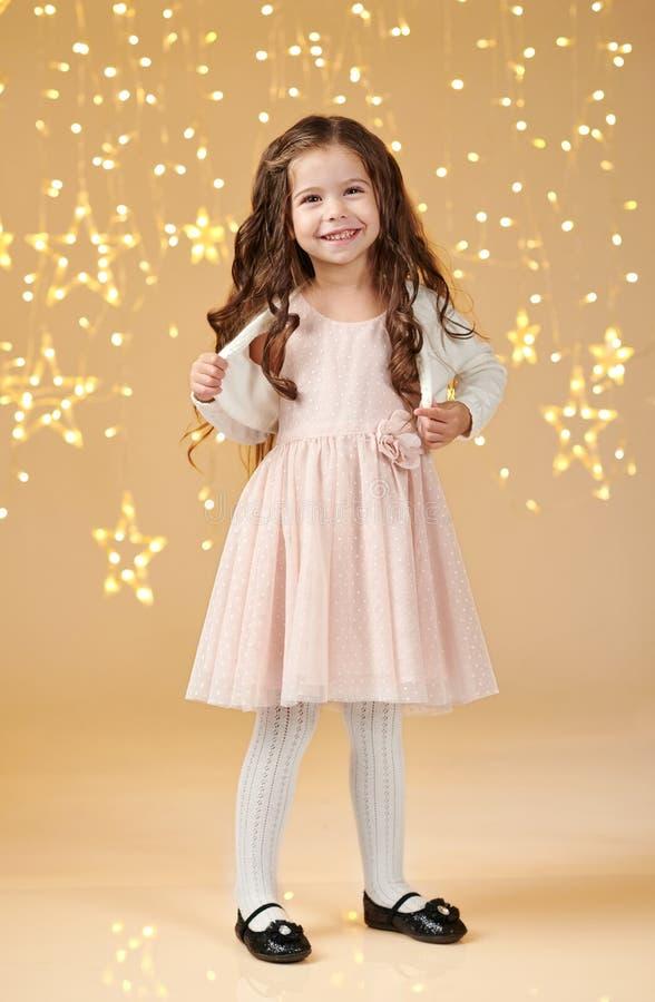 L'enfant de fille est dans des lumières de Noël, fond jaune, robe rose images libres de droits