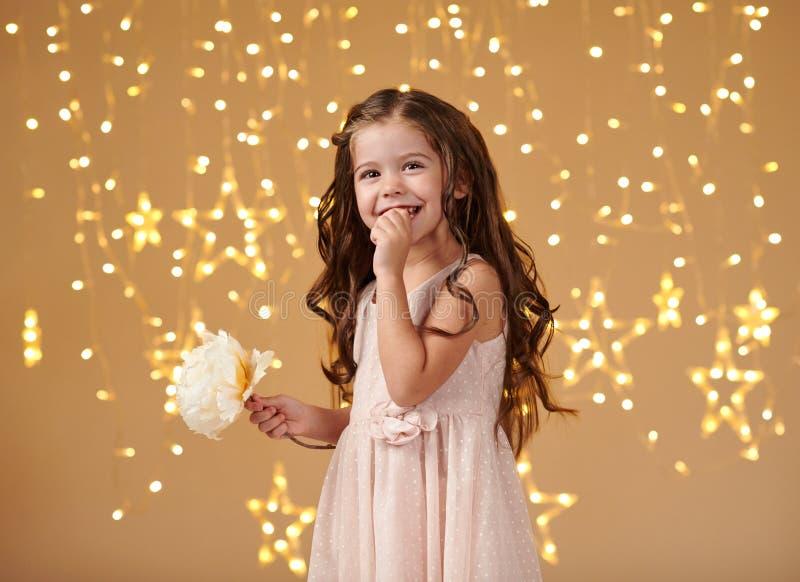 L'enfant de fille est dans des lumières de Noël, fond jaune, robe rose photos libres de droits