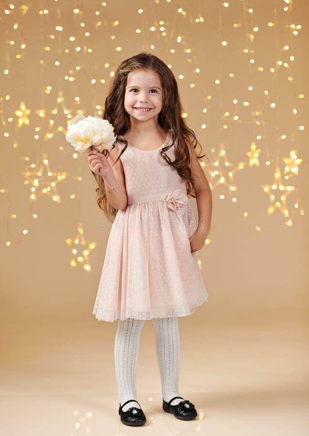 L'enfant de fille est dans des lumières de Noël, fond jaune, robe rose photo libre de droits