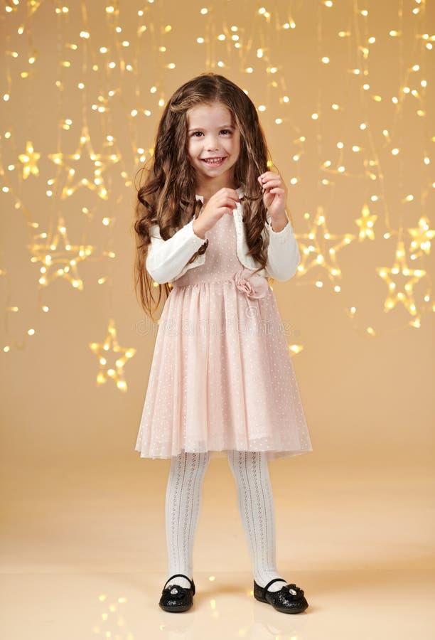 L'enfant de fille est dans des lumières de Noël, fond jaune, robe rose photos stock