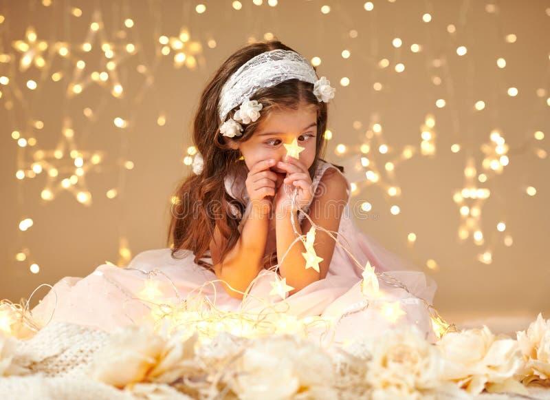 L'enfant de fille joue avec des lumières de Noël, fond jaune, habillé dans la robe rose Elle regarde sur la lumière d'étoile photo libre de droits