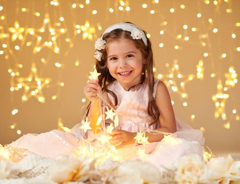 L'enfant de fille joue avec des lumières de Noël, fond jaune, robe rose image stock