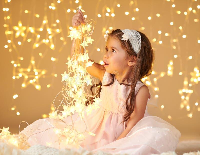 L'enfant de fille joue avec des lumières de Noël, fond jaune, robe rose photographie stock libre de droits