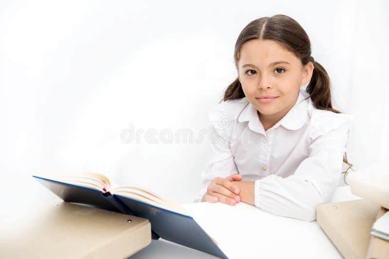 L'enfant de fille a lu le livre reposent l'intérieur blanc de table Écolière étudiant le manuel Le visage heureux d'uniforme scol image libre de droits