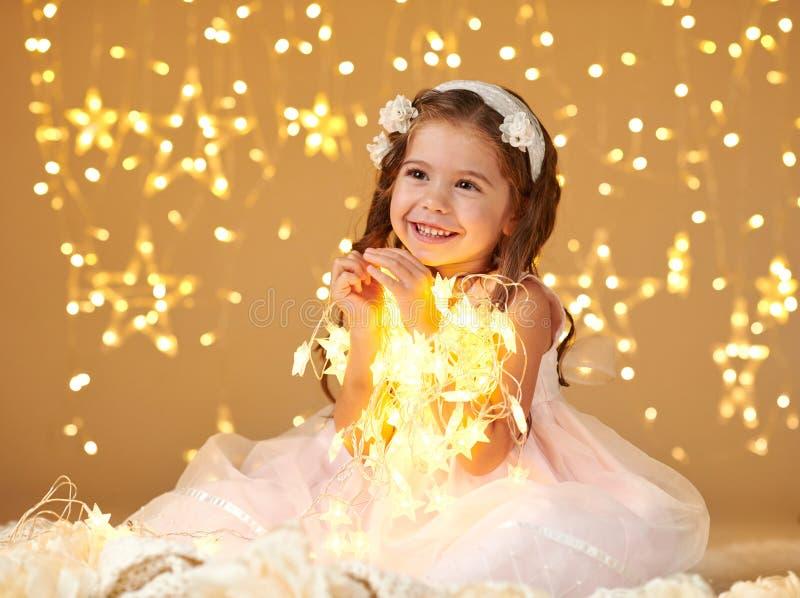 L'enfant de fille pose avec des lumières de Noël, fond jaune, robe rose photographie stock