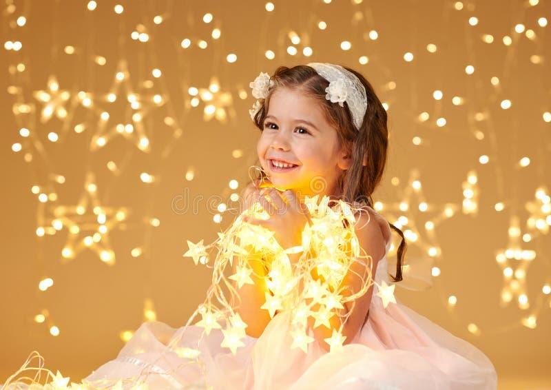 L'enfant de fille pose avec des lumières de Noël, fond jaune, robe rose images libres de droits