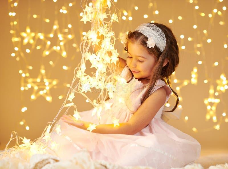 L'enfant de fille pose avec des lumières de Noël, fond jaune, robe rose photos stock