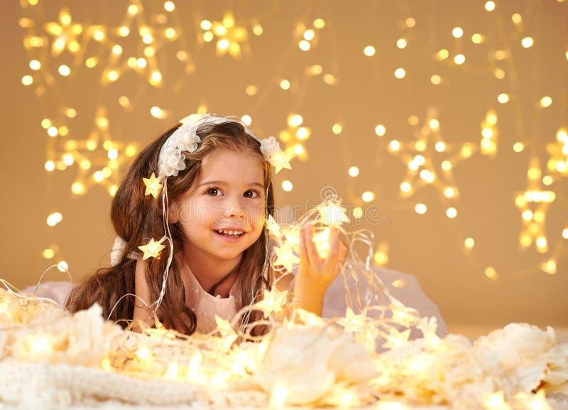 L'enfant de fille pose avec des lumières de Noël, fond jaune, robe rose photo stock