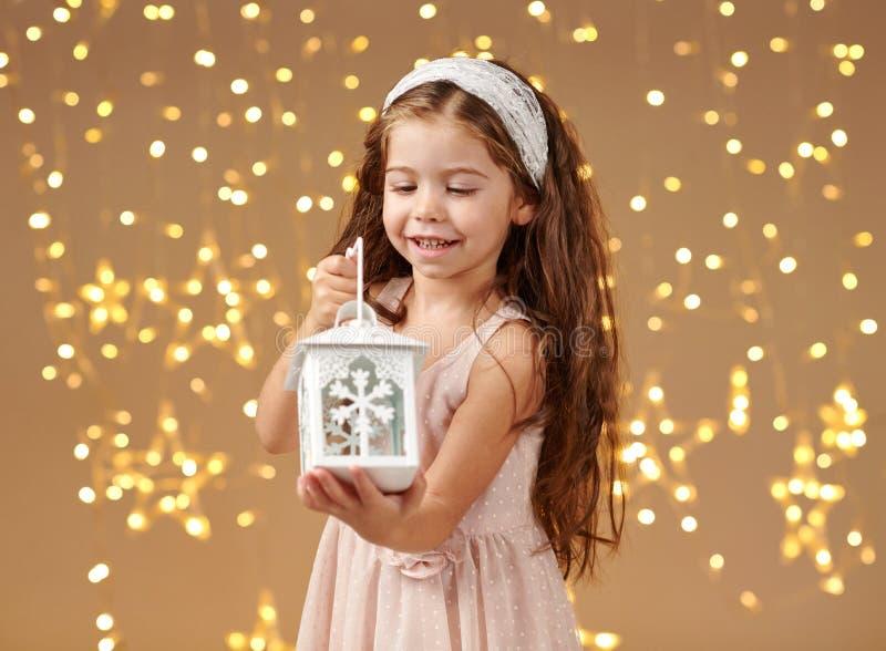 L'enfant de fille pose avec la lanterne dans des lumières de Noël, fond jaune, robe rose photographie stock libre de droits