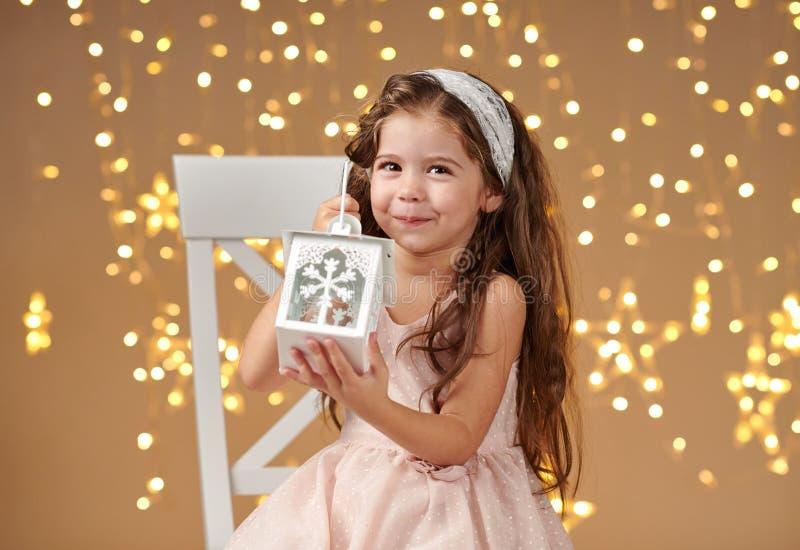 L'enfant de fille pose avec la lanterne dans des lumières de Noël, fond jaune, robe rose images stock