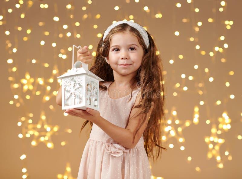 L'enfant de fille pose avec la lanterne dans des lumières de Noël, fond jaune, robe rose photo stock