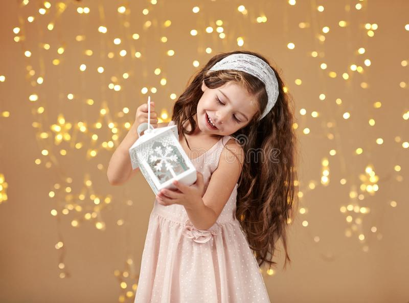 L'enfant de fille pose avec la lanterne dans des lumières de Noël, fond jaune, robe rose photos stock
