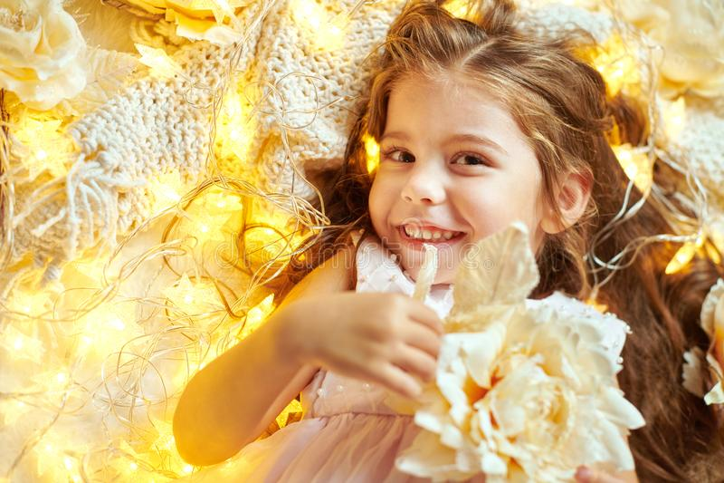 L'enfant de fille se trouve avec des lumières de Noël et des fleurs, plan rapproché de visage image libre de droits