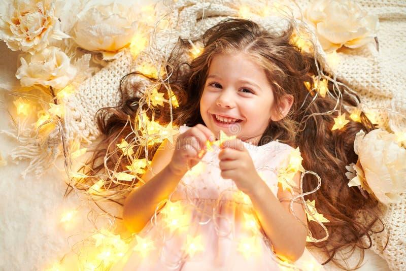 L'enfant de fille se trouve avec des lumières de Noël et des fleurs, plan rapproché de visage photographie stock