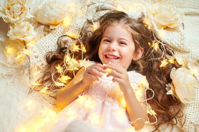 L'enfant de fille se trouve avec des lumières de Noël et des fleurs, plan rapproché de visage photos libres de droits