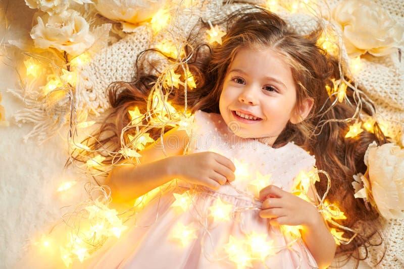 L'enfant de fille se trouve avec des lumières de Noël et des fleurs, plan rapproché de visage photographie stock libre de droits