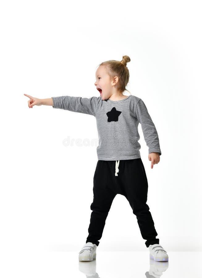 L'enfant de jeune fille a étonné hurler des cris dirigeant le doigt au coin photos libres de droits