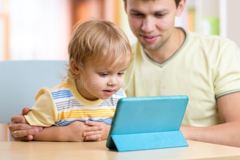 L'enfant de père et de fils jouent avec la tablette à l'intérieur photo stock