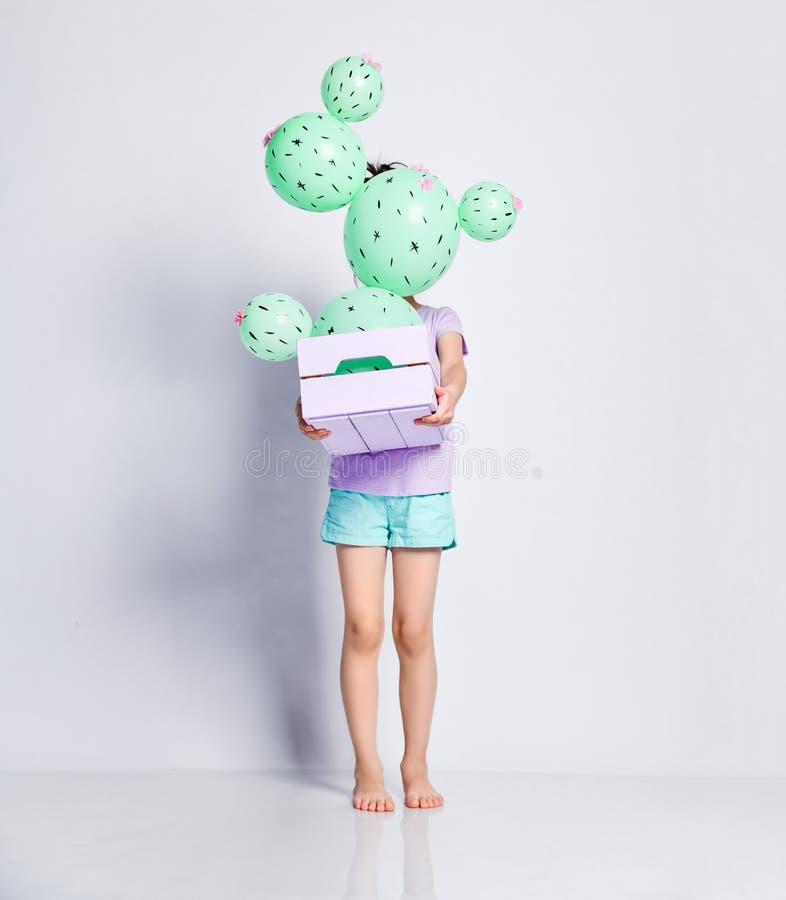L'enfant de petite fille tient une boîte de fleur avec le ballon de cactus avec les fleurs roses ainsi il cache complètement son  photos libres de droits