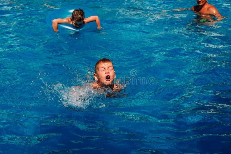 L'enfant de sept ans apprend à nager dans la piscine extérieure photographie stock