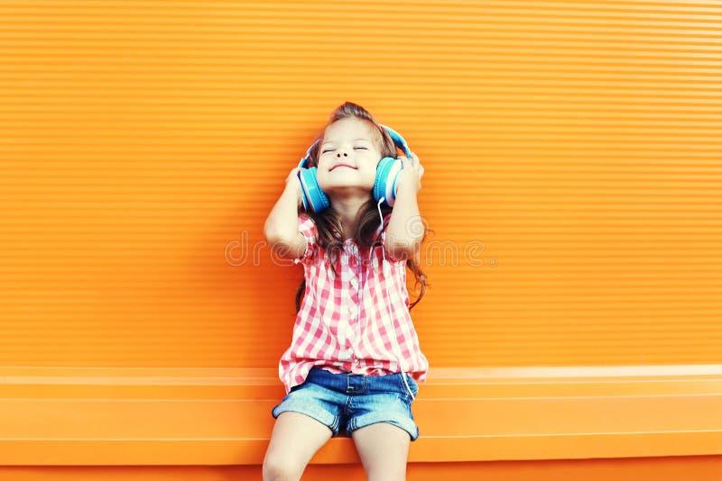 L'enfant de sourire heureux apprécie écoute la musique dans des écouteurs au-dessus d'orange photo libre de droits