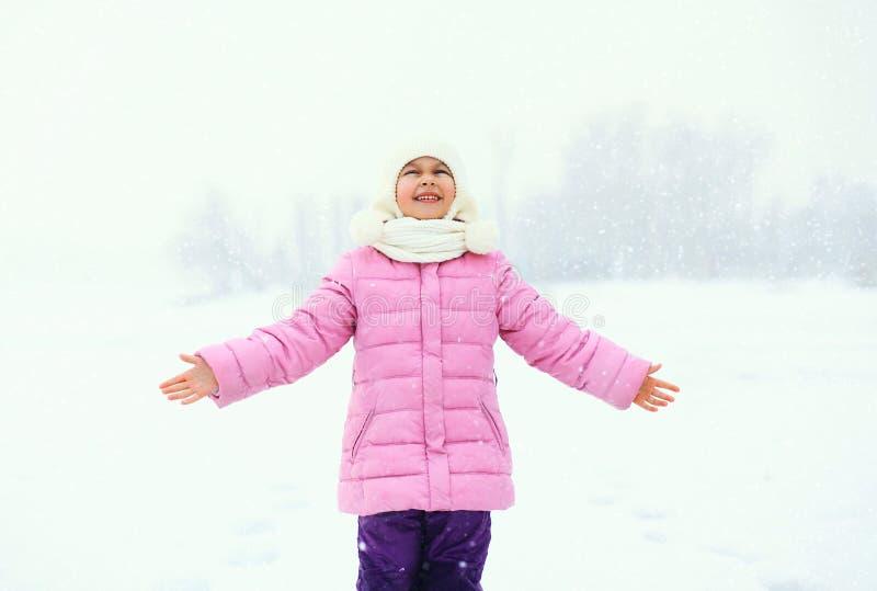 L'enfant de sourire heureux de petite fille apprécie des flocons de neige en hiver image stock