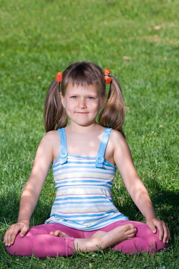 L'enfant de sourire s'asseyent dans l'asana sur l'herbe verte photographie stock libre de droits